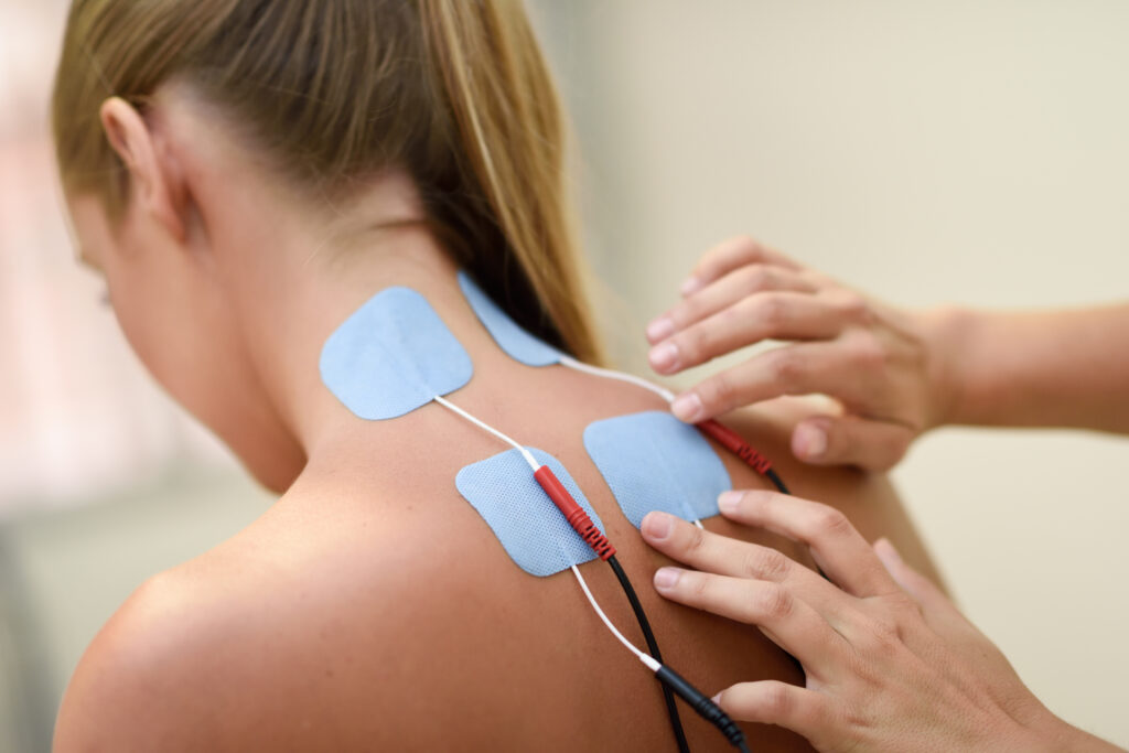 Electro stimulation in physical therapy to a young woman. Medical check at the shoulder in a physiotherapy center.
